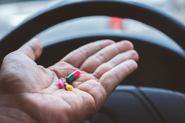 Main de l'homme se drogue dans la voiture
