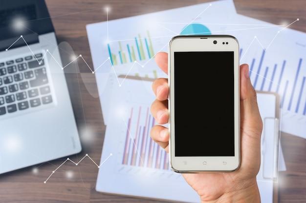 Main d'homme sur smartphone avec fournitures et équipement de bureau