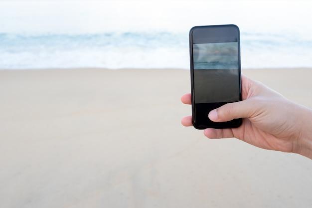 Main d'homme sur smartphone noir sur la belle mer bleue calme et fond de plage de sable fin.