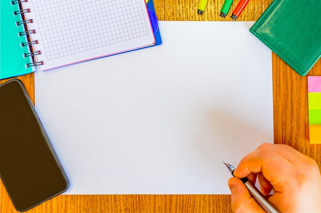 La main de l'homme avec un stylo écrit sur le papier blanc (projet). homme travaillant sur le bureau à l'aide d'un téléphone, d'un bloc-notes, d'un stylo, d'un feutre, d'un journal. faire des plans. organisation du travail.