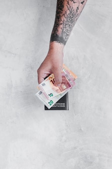 Main de l'homme avec tatouage tenant des billets d'euro et passeport sur le mur de béton