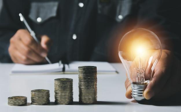 Main d'homme tenant une ampoule avec une pile de pièces pour la comptabilité et le concept créatif.