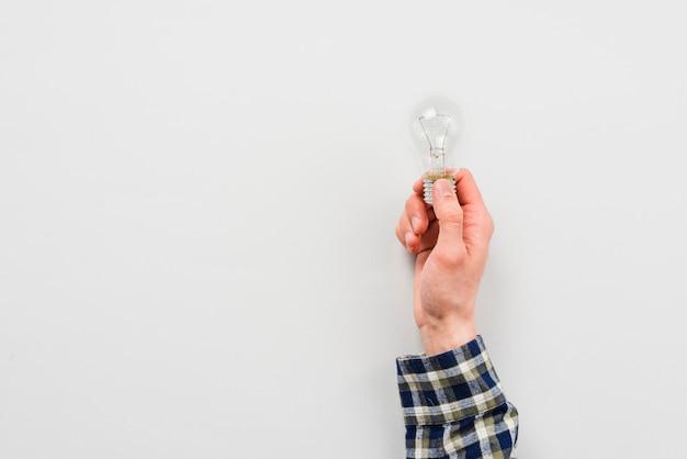 Main d'homme tenant l'ampoule
