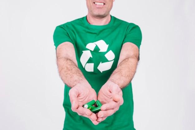 Main de l'homme tenant des batteries vertes