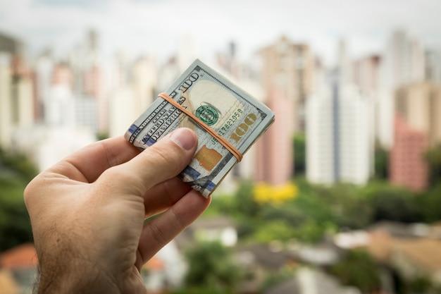 Main d'homme tenant des billets d'un dollar devant un paysage de la ville