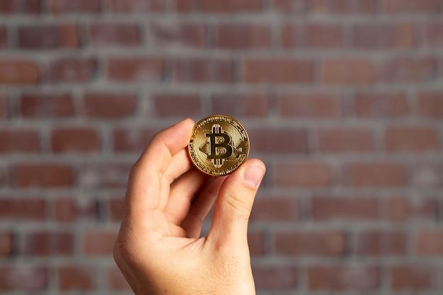 Main de l'homme tenant un bitcoin physique devant un mur de briques