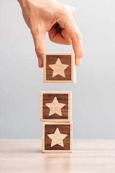 Main d'homme tenant le bloc star. le client choisit la note pour les avis des utilisateurs. notation de service, classement, avis client, satisfaction, évaluation et concept de rétroaction