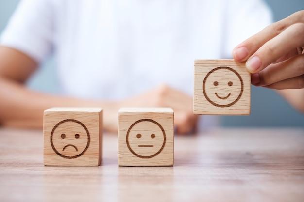 Main d'homme tenant le bloc de visage d'émotion. le client choisit l'émoticône pour les avis des utilisateurs. notation de service, classement, avis client, satisfaction, évaluation et concept de rétroaction