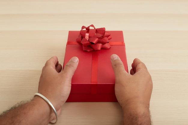 Main d'homme tenant une boîte-cadeau rouge