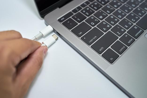 Main de l'homme tenant des câbles usb de type c pour se connecter ou se déconnecter à un ordinateur portable sur blanc