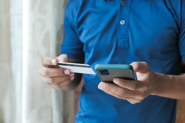Main d'homme tenant une carte de crédit et à l'aide d'un téléphone intelligent, faire des achats en ligne.