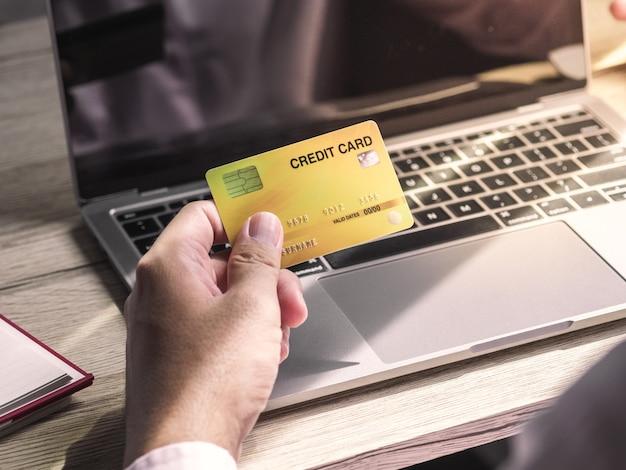 Main d'homme tenant une carte de crédit et utilisant un ordinateur portable. homme d & # 39; affaires travaillant à la maison
