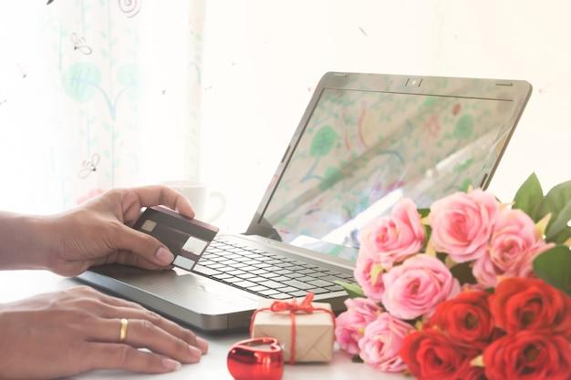 Main d'homme tenant une carte de crédit et utilisant un ordinateur