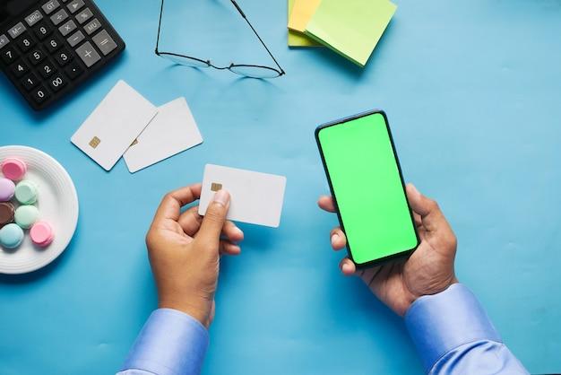 Main d'homme tenant une carte de crédit et utilisant un téléphone intelligent pour faire des achats en ligne