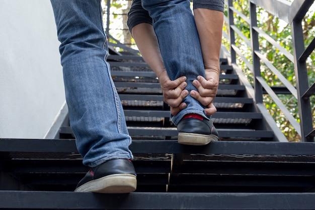 Main d'homme tenant une cheville douloureuse en montant les escaliers.