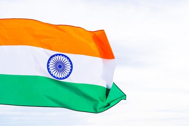 Main d'homme tenant le drapeau de l'inde sur le fond de ciel bleu
