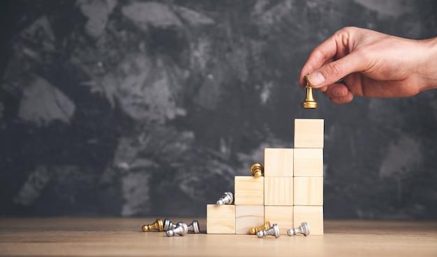 Main de l'homme tenant les échecs sur les blocs