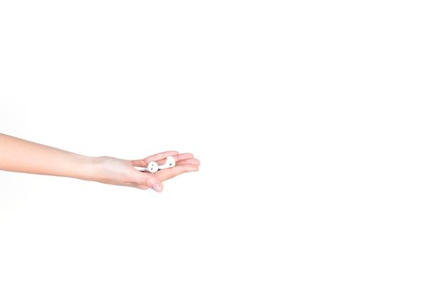 Main de l'homme tenant des écouteurs bluetooth sans fil sur fond blanc