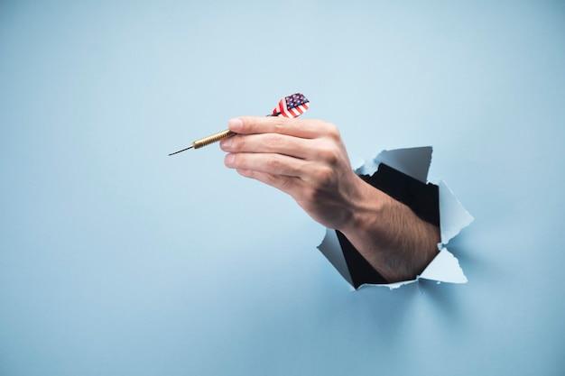 La main de l'homme tenant une fléchette sur une scène bleue
