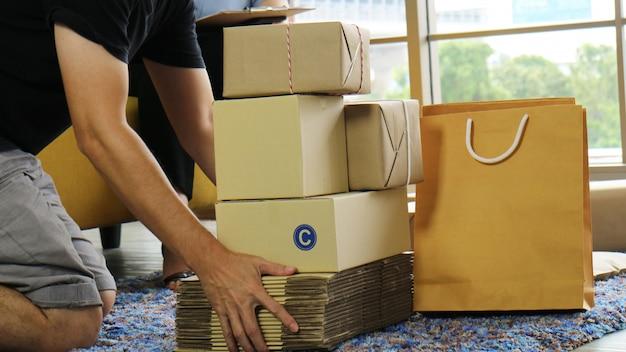 Main d'homme tenant un groupe de colis de produits à envoyer au client.