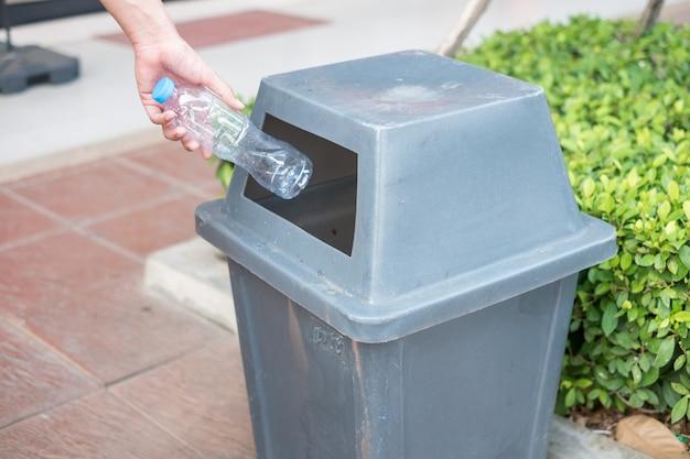 Main d'homme tenant et mettant les déchets de la bouteille en plastique à la poubelle.