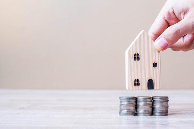 Main d'homme tenant le modèle de maison en bois sur la pile de pièces