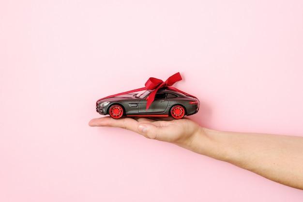 Main de l'homme tenant le modèle de voiture jouet attaché avec un ruban rouge et un arc sur fond rose. concession automobile et location, voiture comme cadeau ou cadeau, tirage de voiture, chance de gagner un concept de voiture moderne