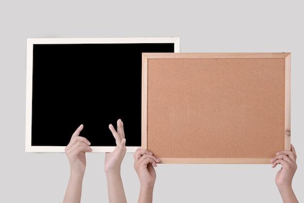 Main de l'homme tenant un panneau de liège brun dans un cadre et tableau noir isolé sur mur blanc