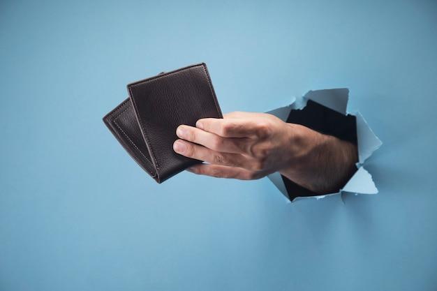 Main de l'homme tenant le portefeuille sur la scène bleue