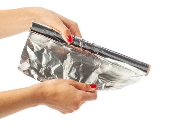 Main de l'homme tenant un rouleau de papier d'aluminium isolé sur blanc