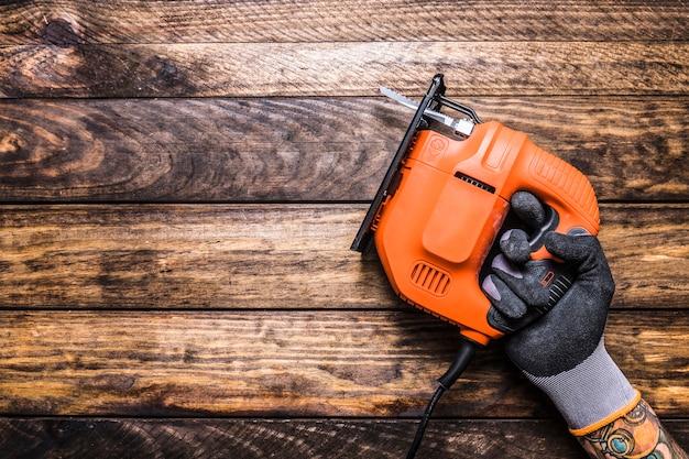 Main de l'homme tenant une scie sauteuse électrique sur fond en bois