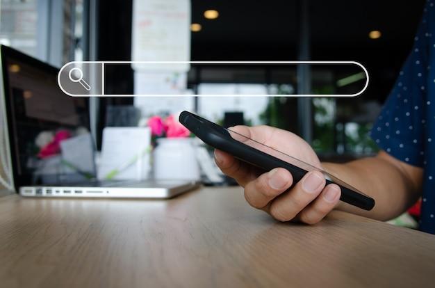Main de l'homme tenant un smartphone à la recherche de réseau social