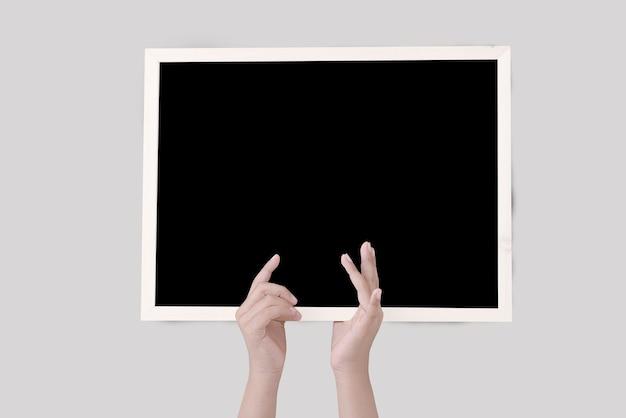 Main de l'homme tenant le tableau noir isolé sur mur blanc
