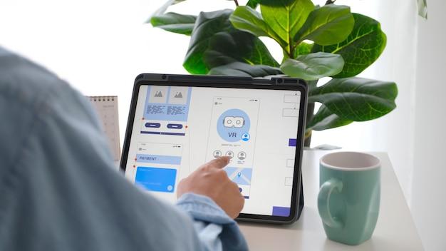 Main d'homme tenant une tablette numérique avec un prototype de développement d'applications mobiles tout en travaillant à la maison