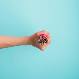 Main de l'homme tenant des tas de crayons colorés sur fond bleu