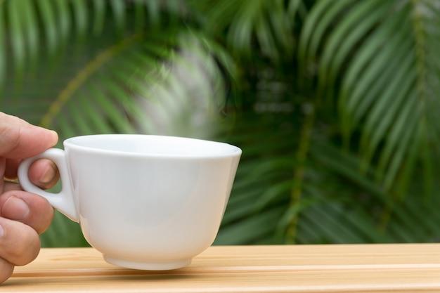 Main d'homme tenant une tasse de café blanche sur une table en bois et un palmier en arrière-plan.