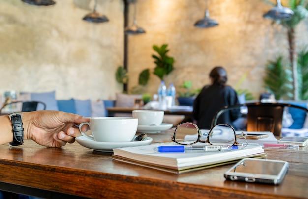 Main d'homme tenant une tasse à café avec des lunettes de lecture, téléphone portable sur la table.