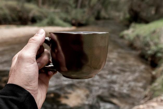Main de l'homme tenant une tasse dans la forêt, concept d'automne