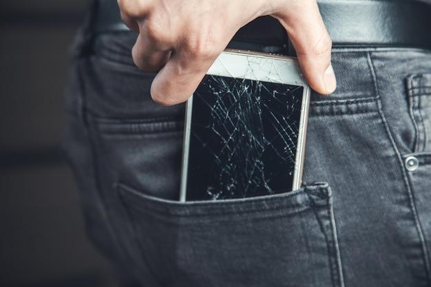Main de l'homme tenant un téléphone cassé dans la poche