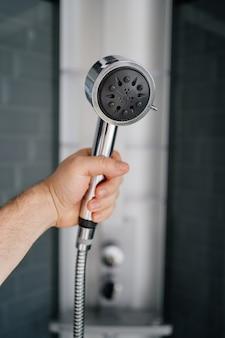 La main d'un homme tient l'arrosoir de la douche. plomberie moderne pour la salle de bain et la douche. magasin d'articles pour la maison.