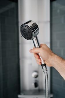 La main d'un homme tient l'arrosoir de la douche. plomberie moderne pour la salle de bain et la douche