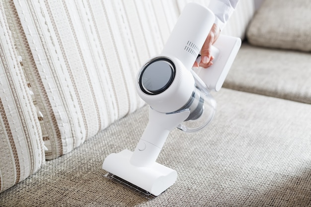 La main d'un homme tient un aspirateur sans fil moderne pour nettoyer le canapé de la maison.