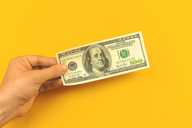 La main de l'homme tient un billet de cent dollars sur fond jaune de table de bureau, concept de dépôt bancaire