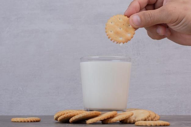 La main de l'homme tient un biscuit au-dessus du lait sur une table en marbre.