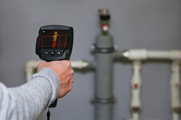 La main d'un homme tient une caméra thermique, vérifiant le système de chauffage d'une maison.