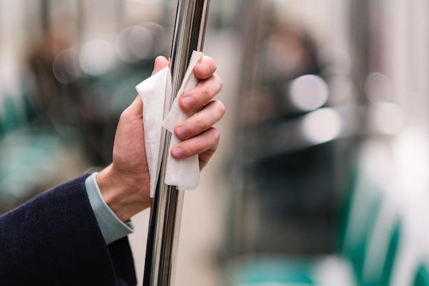 Main de l'homme tient une main courante dans les transports en commun / métro à travers une serviette