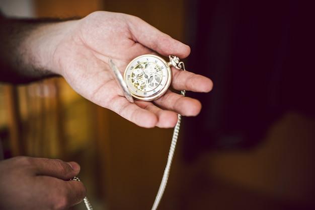 Une main d'homme tient une montre de poche ancienne avec ses engrenages et sa main en vue.