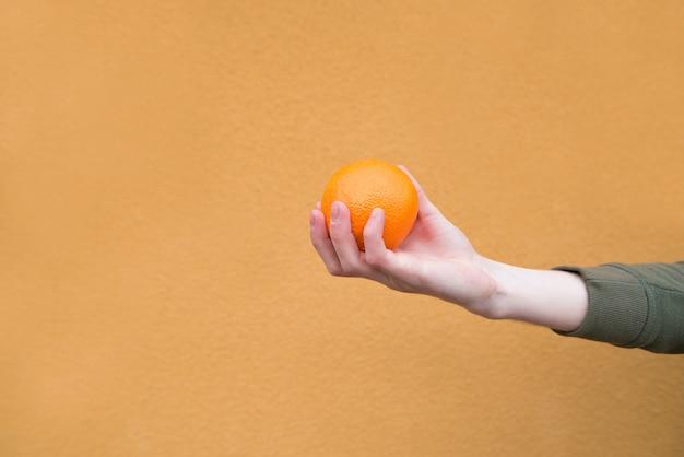 La main de l'homme tient une orange sur un mur orange. le concept est un homme et un fruit