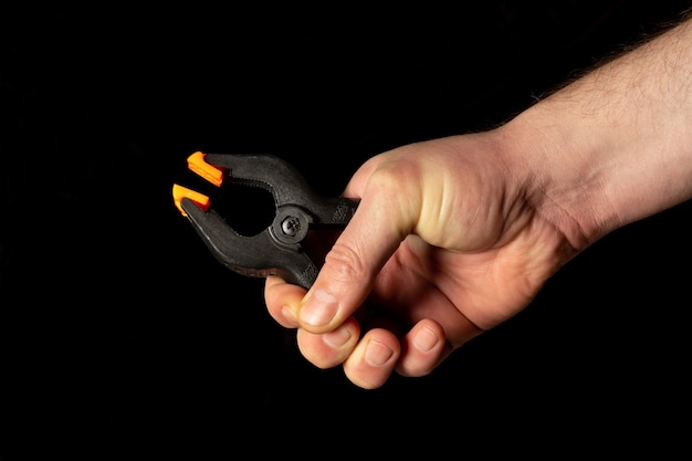 La main de l'homme tient des pinces à ressort en plastique