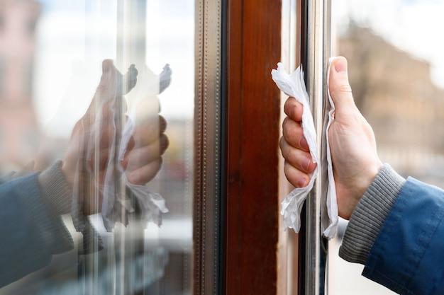 La main de l'homme tient la poignée de porte à travers une serviette, pour réduire le risque d'infection par contact avec des germes, coronavirus